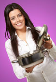 Portrait of young girl opening sauce pan over purple background — Stock Photo