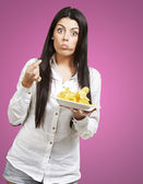 Young woman eating potatoe chips against a pink background — Stock Photo