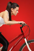 Young sporty girl cycling over red background — Stock Photo