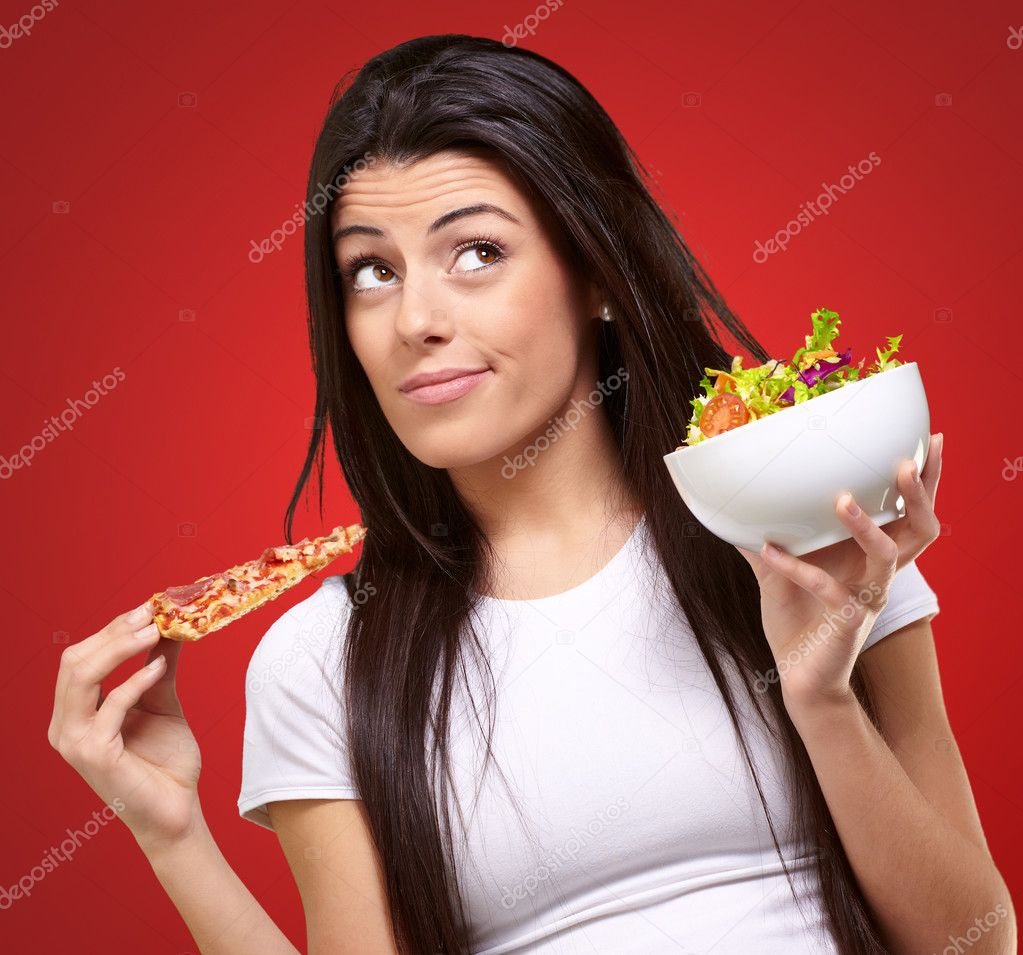 Portrait of young woman choosing pizza or salad against a red background — Stock Photo #13310603