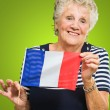 Happy Senior Woman Holding France Flag - Stock Photo