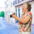 Happy Senior Woman Holding Camera — Stock Photo #13362813