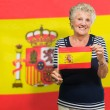 Senior Woman Holding Spain Flag - Stock Photo