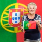 Senior mujer sosteniendo la bandera de portugal — Foto de Stock