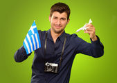 Man Holding A Miniature Airplane And Greece Flag — Stock Photo