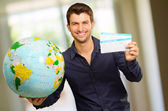 A Young Man Holding Boarding Pass And Globe — Stock Photo