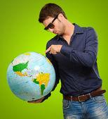 Dünya üzerinde bir işaret eden genç bir adam — Stok fotoğraf