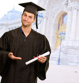 Young Man In Graduation Gown Holding Certificate — Stockfoto
