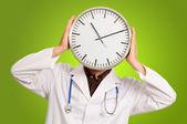 Doktor gizli yüz ile masa saati — Stok fotoğraf