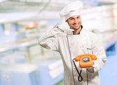 Ritratto di uno chef tenendo il telefono e fare Identificativo — Foto Stock