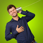 Man Listening From Tin Can Telephone against a green background — Stock Photo