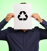 Young Man Holding A Recyclable Symbol In Front Of Face — Stock Photo