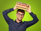 小伙子手持堆在头上的书 — 图库照片