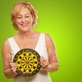 Happy Mature Woman Holding Dartboard — Stock Photo