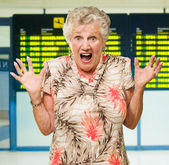 Shocked Senior Woman In Front Of Airport Arrival And Departure B — Stock Photo