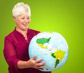 Sênior mulher segurando um globo — Fotografia Stock