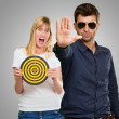 Man Making Hand Stop And Afraid Woman Holding Dartboard — Stock Photo