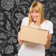 Stock Photo: WomHolding Cardboard box