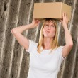 Woman holding a box on her head — Stock Photo