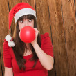 Christmas woman blowing a balloon with her eyes crossed - Stock Photo