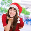 Woman wearing a christmas hat and blowing a kiss — Stock Photo #14055044