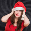 Stock Photo: Worried woman wearing a christmas hat