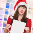 Stock Photo: Worried christmas woman holding a blank card