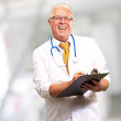 Stock Photo: Happy Male Doctor Writing On Clipboard