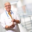 Male Doctor Putting Coins In A Piggy Bank — Stock Photo #14056329