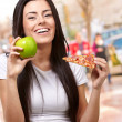 Female Holding A Piece Of Pizza And A Apple — Stock Photo #14057157