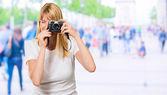 Mujer mirando a través de la vieja cámara — Foto de Stock