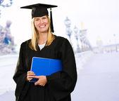 Glückliche diplom frau hält eine notebook — Stockfoto