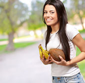 Young Girl Holding Banana And Coconut — Stock Photo