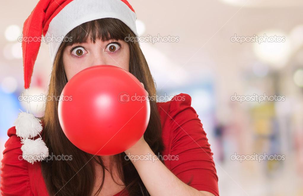 吹气球和戴着圣诞帽子的女人