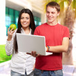 Students holding laptop and fruit — Stock Photo #14426079