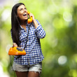 Portrait of young woman talking on vintage telephone against a n — Stock Photo