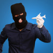 Man wearing robber mask and holding airplane miniature — Stock Photo #14423669