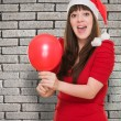 Surprised woman wearing a christmas hat and holding a balloon — Stock Photo #14425321