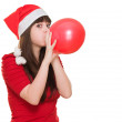 Woman wearing a christmas hat and blowing a balloon — Stock Photo #14425331