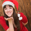 Woman wearing a christmas hat and blowing a kiss — Stock Photo