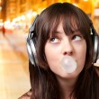 Portrait of young woman listening to music with bubble gum at ni — Stock Photo