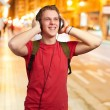Portrait of cheerful young student listening music with headphon — Stock Photo #14427343