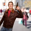 Portrait of young man holding beer at crowded street — Stock Photo #14427637