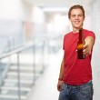 Portrait of young man holding beer at entrance of modern buildin — Stock Photo #14427647