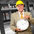 Portrait Of A Senior Man Holding A Wall Watch — Stock Photo #14429621