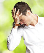 Angry young man doing frustration gesture against a nature backg — Stock Photo