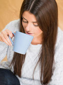 Beautiful woman holding a blue mug — Stock Photo
