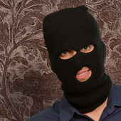 Man wearing a robber mask showing a blank paper — Stock Photo