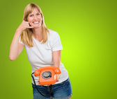 Woman holding telephone and doing a gesture — Stock Photo