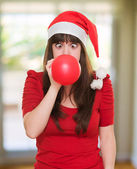Christmas woman blowing a balloon with her eyes crossed — Stock Photo